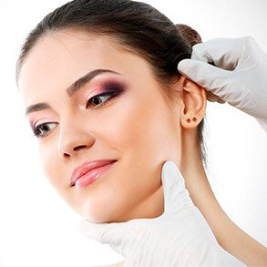 Mãos tocando cabeça de mulher com luvas cirúrgicas